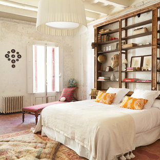 Example of a large tuscan master terra-cotta floor and red floor bedroom design in Other with white walls