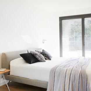 Imagen de habitación de invitados minimalista con paredes blancas, suelo de madera en tonos medios y suelo beige