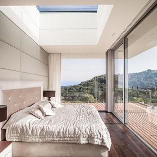 Foto de dormitorio principal, minimalista, con suelo de madera oscura, paredes blancas y suelo marrón