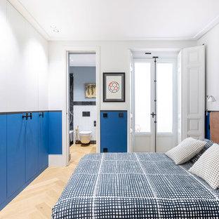 Foto de dormitorio contemporáneo con paredes blancas, suelo de madera clara y suelo beige