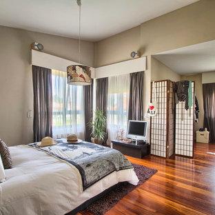 Ejemplo de dormitorio principal, asiático, de tamaño medio, sin chimenea, con paredes beige y suelo de madera en tonos medios