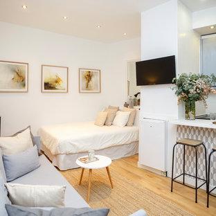 Modelo de dormitorio marinero con paredes blancas, suelo de madera clara y suelo beige