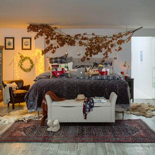 Modelo de dormitorio principal, campestre, grande, con paredes blancas, suelo de madera clara y suelo gris
