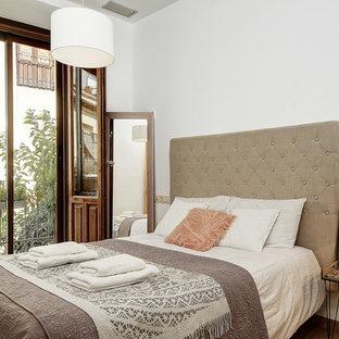 Foto de habitación de invitados mediterránea con paredes blancas, suelo de madera en tonos medios y suelo marrón
