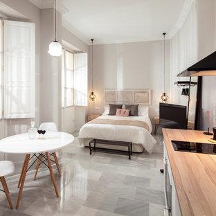 Imagen de dormitorio tipo loft, minimalista, de tamaño medio, sin chimenea, con paredes grises, suelo de mármol y suelo blanco