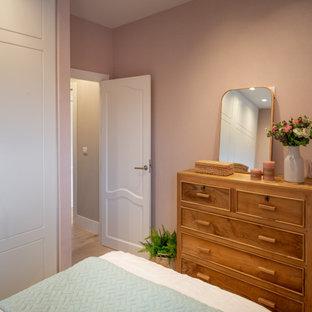 Modelo de habitación de invitados bandeja y papel pintado, actual, pequeña, sin chimenea, con paredes rosas, suelo laminado, suelo marrón y papel pintado