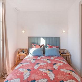 Diseño de dormitorio costero con paredes blancas, suelo de madera en tonos medios y suelo marrón
