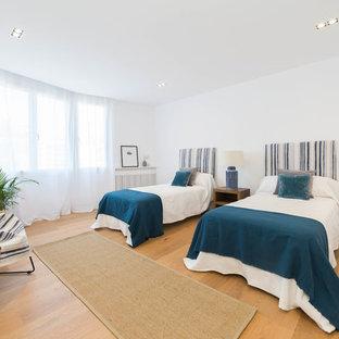 Modelo de dormitorio mediterráneo con paredes blancas y suelo de madera en tonos medios