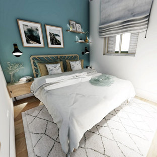 Imagen de dormitorio principal, urbano, pequeño, sin chimenea, con paredes azules, suelo laminado y suelo marrón