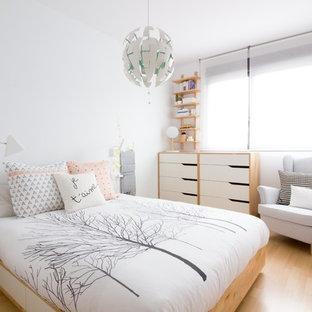 Imagen de dormitorio nórdico, de tamaño medio, con paredes blancas, suelo de madera en tonos medios y suelo marrón