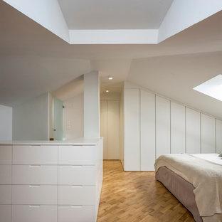 Foto de dormitorio actual con paredes blancas, suelo de madera clara y suelo marrón