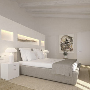 Photo of a large mediterranean master bedroom in Palma de Mallorca with white walls, medium hardwood floors, no fireplace, brown floor and exposed beam.
