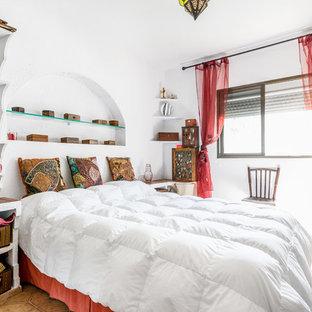 Imagen de habitación de invitados exótica con paredes blancas y suelo marrón