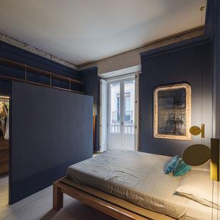Modelo de dormitorio principal, contemporáneo, de tamaño medio, con paredes azules, suelo de cemento y suelo azul