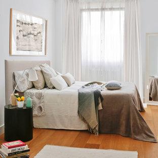 Modelo de dormitorio principal, contemporáneo, pequeño, sin chimenea, con paredes blancas, suelo de madera en tonos medios y suelo naranja