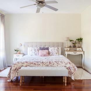 Imagen de dormitorio romántico con paredes beige, suelo de madera en tonos medios y suelo marrón