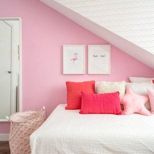 Modelo de dormitorio actual con paredes rosas, suelo de madera oscura y suelo marrón