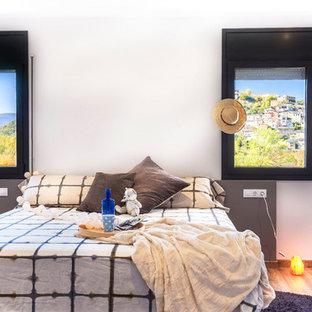 他の地域のコンテンポラリースタイルのおしゃれな客用寝室 (白い壁、コルクフローリング、茶色い床)