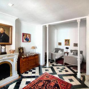 Ejemplo de dormitorio mediterráneo con paredes blancas, chimenea tradicional y suelo multicolor