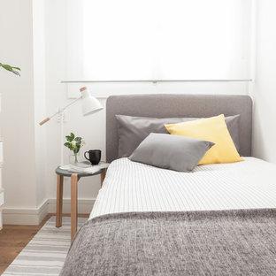 Modelo de habitación de invitados actual, pequeña, con paredes blancas, suelo de madera en tonos medios y suelo marrón
