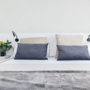 Ispirazione per una camera matrimoniale nordica di medie dimensioni con pareti bianche, pavimento in laminato, nessun camino e pavimento marrone
