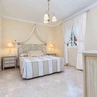 Example of a mid-sized classic master travertine floor bedroom design in Malaga with beige walls and no fireplace