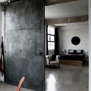 Bedroom - large industrial master concrete floor bedroom idea in Valencia with white walls and no fireplace