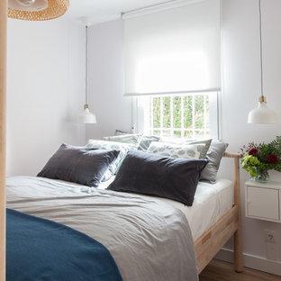 Ejemplo de dormitorio tipo loft, nórdico, pequeño, con paredes blancas, suelo laminado y suelo marrón