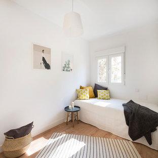 Ejemplo de dormitorio escandinavo con paredes blancas, suelo de madera en tonos medios y suelo marrón