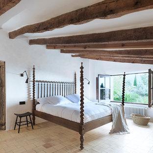 Ejemplo de dormitorio principal, mediterráneo, con paredes blancas, chimenea de esquina, marco de chimenea de yeso y suelo beige