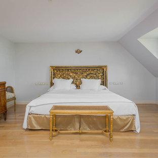 Foto de dormitorio principal, clásico, de tamaño medio, con paredes blancas, suelo de madera clara y suelo beige