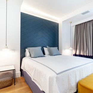 Ejemplo de habitación de invitados contemporánea, sin chimenea, con paredes blancas y suelo de madera en tonos medios
