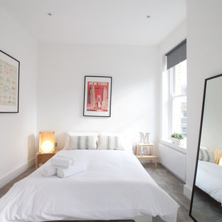 Design ideas for a scandinavian guest bedroom in London with white walls, carpet and grey floors.