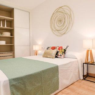 Imagen de dormitorio principal, actual, de tamaño medio, con paredes blancas, suelo beige y suelo de madera clara