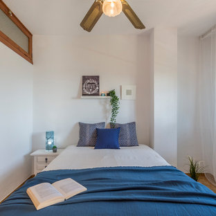 Photo of a mid-sized beach style master bedroom in Other with white walls, terra-cotta floors and beige floor.