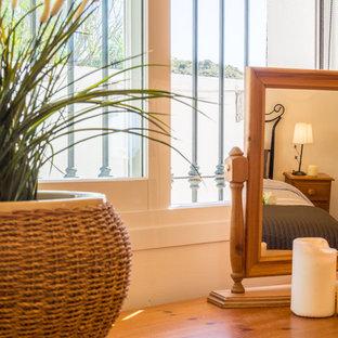 Foto de habitación de invitados mediterránea, de tamaño medio, con paredes beige, suelo de baldosas de terracota y suelo marrón
