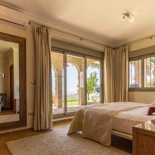 Cette photo montre une chambre parentale méditerranéenne de taille moyenne avec un mur beige, un sol en carrelage de céramique, un poêle à bois et un sol beige.