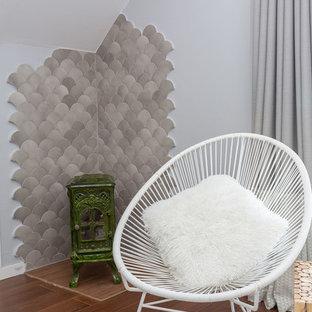 Imagen de habitación de invitados mediterránea, grande, con paredes grises, suelo de madera en tonos medios, estufa de leña, marco de chimenea de baldosas y/o azulejos y suelo marrón