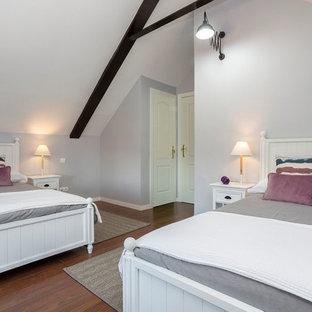 Réalisation d'une grande chambre d'amis méditerranéenne avec un mur gris, un sol en bois brun, un sol marron, un poêle à bois et un manteau de cheminée en carrelage.