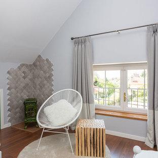 Cette image montre une grand chambre d'amis méditerranéenne avec un mur gris, un sol en bois brun, un sol marron, un poêle à bois et un manteau de cheminée en carrelage.