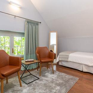Foto de habitación de invitados mediterránea, grande, con paredes grises, suelo de madera en tonos medios y suelo marrón