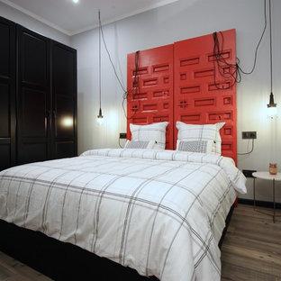 Foto de dormitorio industrial con paredes grises, suelo de madera oscura y suelo marrón