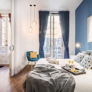 Modelo de dormitorio principal, actual, con paredes blancas, suelo de madera en tonos medios y suelo marrón