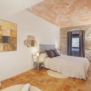 Стильный дизайн: хозяйская спальня среднего размера в средиземноморском стиле с белыми стенами и полом из терракотовой плитки без камина - последний тренд