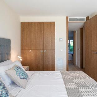 Ejemplo de habitación de invitados mediterránea con paredes blancas, suelo de madera clara y suelo beige