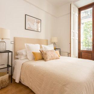Imagen de dormitorio mediterráneo con paredes blancas, suelo de madera en tonos medios y suelo marrón