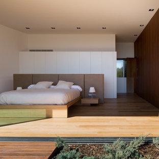 Modelo de dormitorio principal, contemporáneo, con suelo de madera clara, paredes blancas y suelo beige