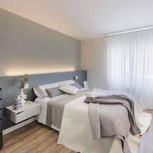 Modelo de dormitorio actual, grande, sin chimenea, con paredes grises, suelo de madera en tonos medios y suelo marrón