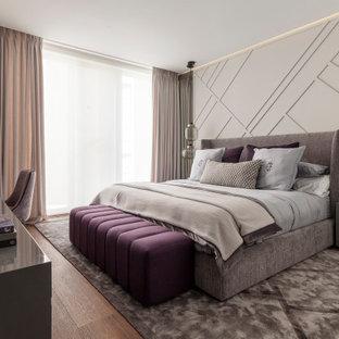 Ejemplo de dormitorio principal, actual, grande, sin chimenea, con paredes grises, suelo de madera en tonos medios y suelo marrón