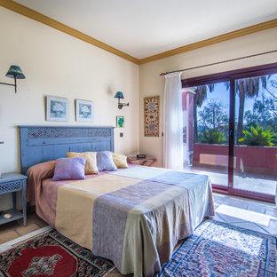 Diseño de dormitorio principal, bohemio, de tamaño medio, sin chimenea, con suelo de baldosas de terracota y paredes amarillas